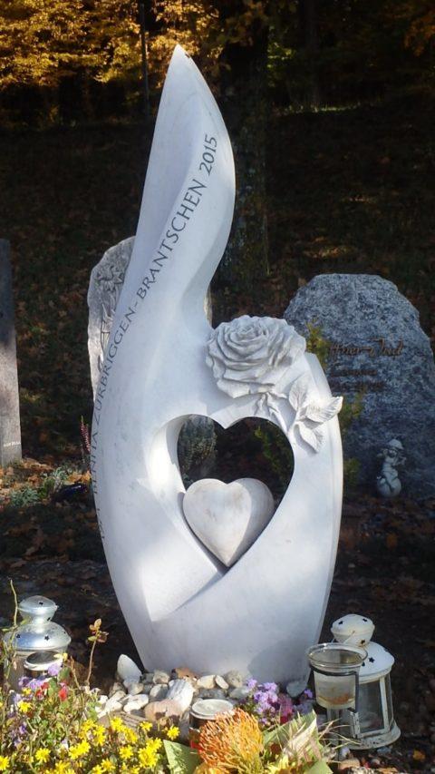 Moderner, spezieller Grabstein mit Herzdurchbruch, Steinherz und einer Rose als Relief