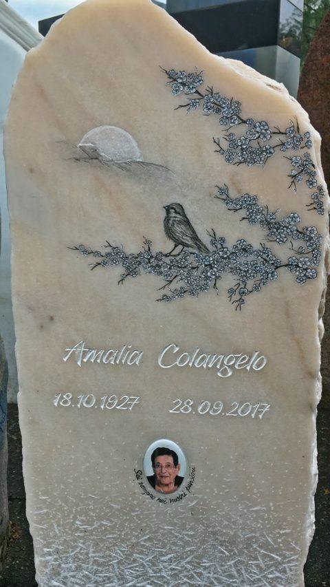 Grabstein aus Estremoz mit einem Spatz auf Kirschbaum in Blüte und der Sonne
