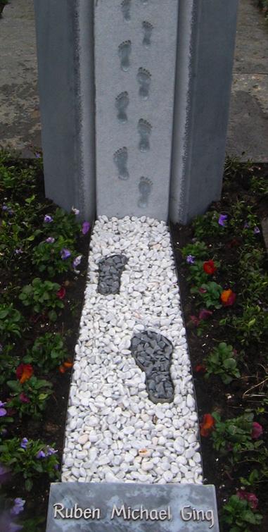 Grabgestaltung mit Edelstahl und weissem, sowie grauem Kies. Mit Fussspuren passend zum Grabmal.