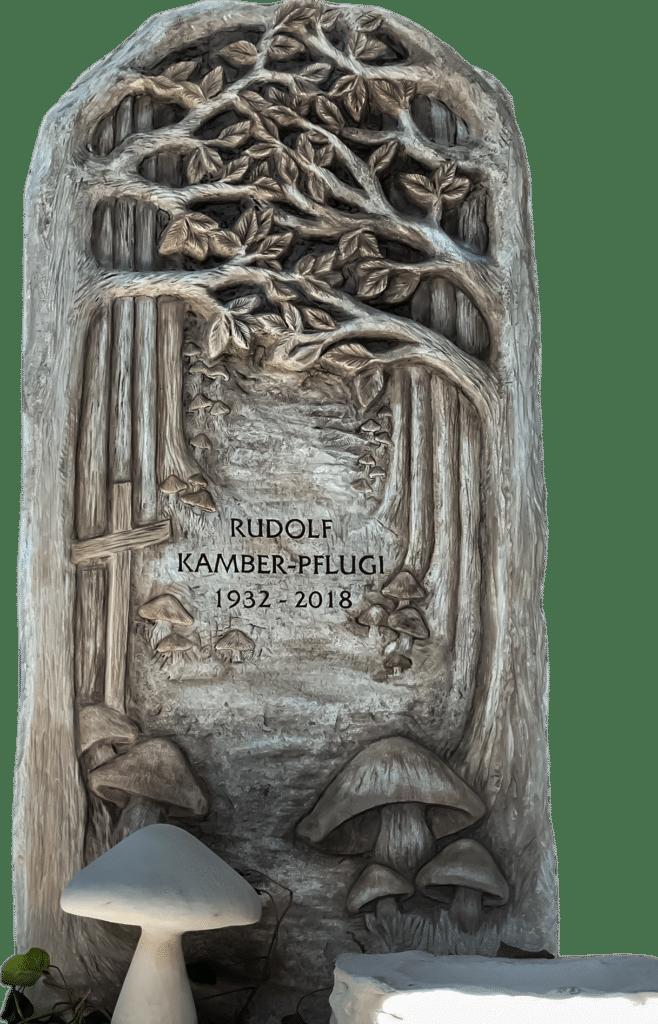 Detaillierter Grabstein aus Crevola Marmor mit einem Pilzwald und Wegkreuz als Relief. Mit vorgelagerter vollplastischer Pilzskulptur als Grabschmuck.