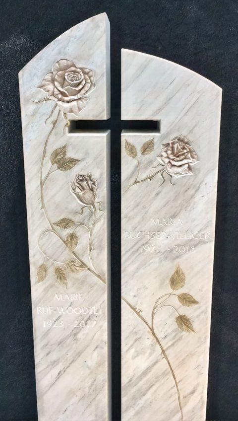 zweiteiliger Grabstein aus Crevola Marmor mit kreuzförmigem Ausschnitt und Rosenranken, patiniert und als Flachrelief ausgeführt.