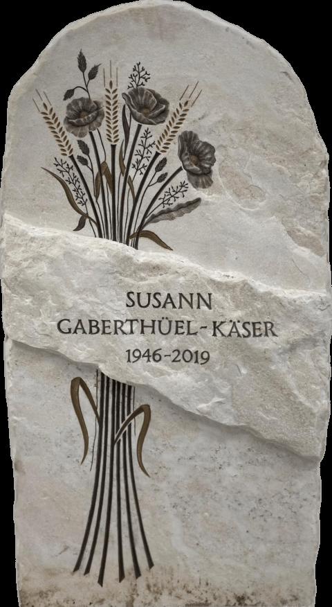 Klassischer Grabstein aus Crevola Palissandro Krustenmarmor. Das naturbelassene Band in der Mitte dient als Schriftträger. Die herabgesetzten Flächen haben wir mit einer Reliefgravur eines Blumenstrausses mit Mohblumen und Ähren versehen.