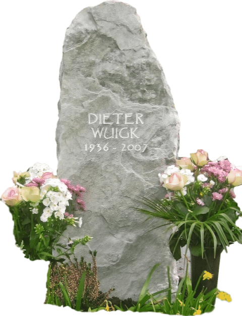 Naturbelassener Grabstein aus Kalkstein mit gravierter Inschrift und bruchroher Oberfläche