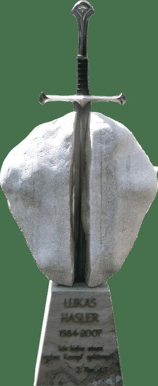 Grabstein aus Marmor mit einem Schwert, dass den Grabstein spaltet. In Anlehnung an Exkalibur.