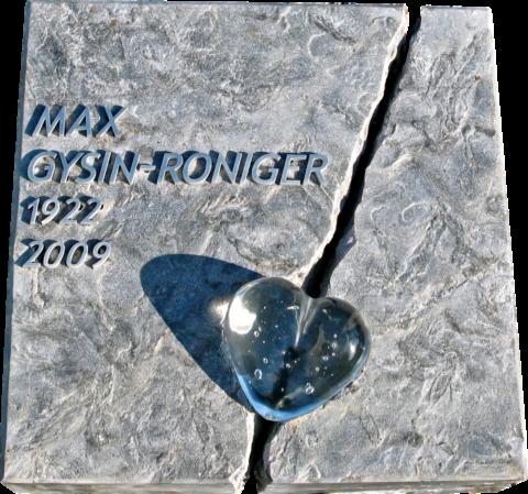 Grabliegeplatte mit Aluminiumschrift auf gebürstetem Silver Shadow. Durch die Platte geht ein Riss, daraufliegend ein Herz aus Glas.