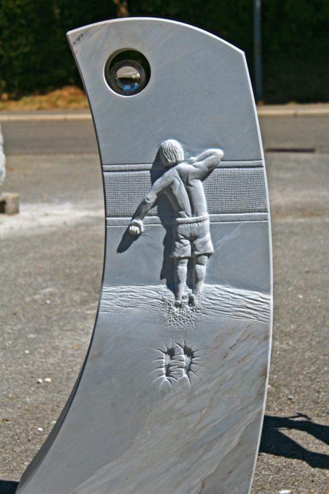 Grabstein aus Crevola Bluette Marmor mit einem Volleyballspieler mit Netz als Relief, der Ball wird durch die Glaskugel symbolisiert